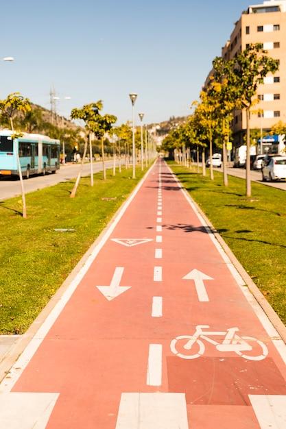 Flechas direccionales y signo de bicicleta en carril de ciclo de perspectiva en disminución Foto gratis