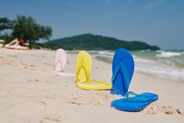 Flip-flops en la playa de arena Foto Premium