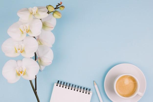 Flor blanca pura de la orquídea; bloc de notas espiral lápiz y taza de café sobre fondo azul Foto gratis