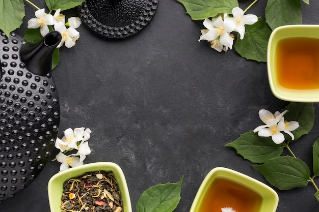 Flor blanca y té de hierbas secas dispuestas en marco sobre fondo negro Foto gratis