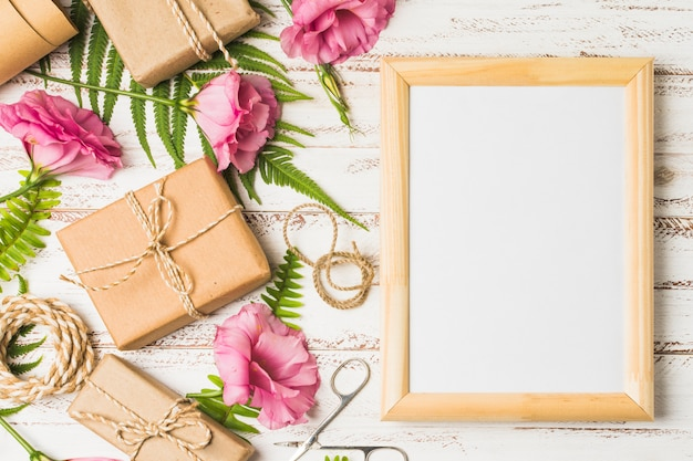 Flor de eustoma y regalos empaquetados con marco vacío en mesa. Foto gratis