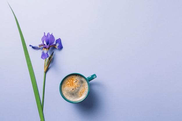 Flor de iris blueflag con taza de café sobre superficie púrpura Foto gratis