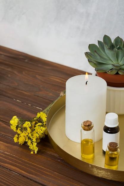 Flor de limonio con una vela grande e iluminada blanca y una botella de aceite esencial en el escritorio de madera Foto gratis