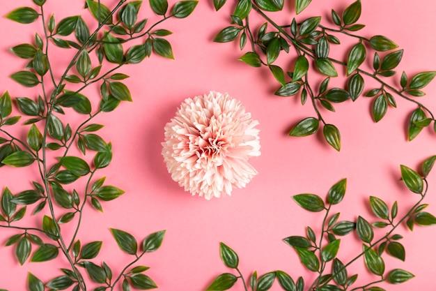 Flor rosa con marco de hojas Foto gratis