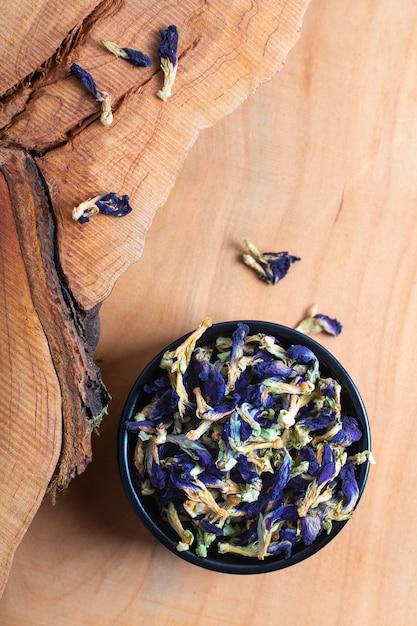 La flor seca del guisante de mariposa del concepto de la comida para hace el té herbario en taza de cerámica en el tablero de madera Foto Premium