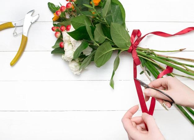 Floreria femenina haciendo hermoso ramo en florería Foto gratis