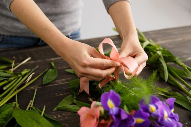 Floreria haciendo ramo de flores, sujete la cinta Foto gratis