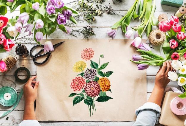 Floreria que muestra el diseño vacío espacio que el papel en la mesa de madera con las flores frescas adorna Foto gratis