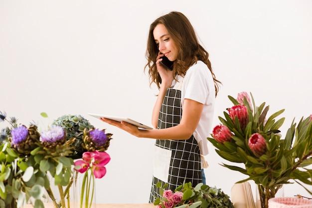 Floreria de tiro medio con teléfono inteligente y tableta Foto gratis