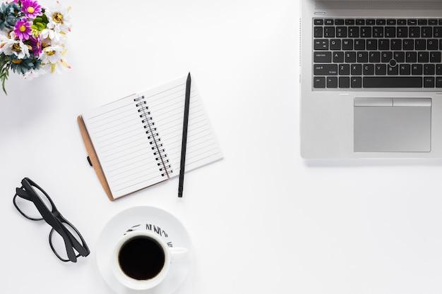 Florero; los anteojos; diario; lápiz y taza de café con ordenador portátil sobre fondo blanco Foto gratis
