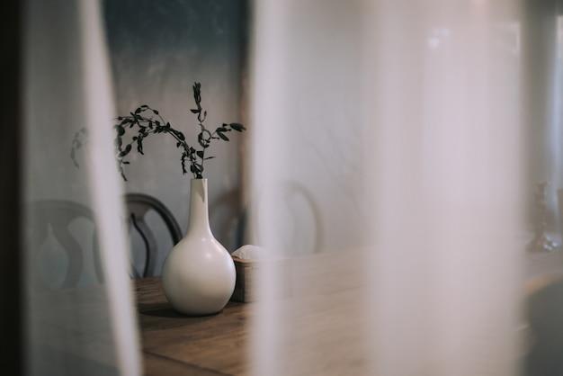 El florero blanco con la rama seca se coloca en la tabla de madera. el diseño minimalista de la habitación. Foto Premium