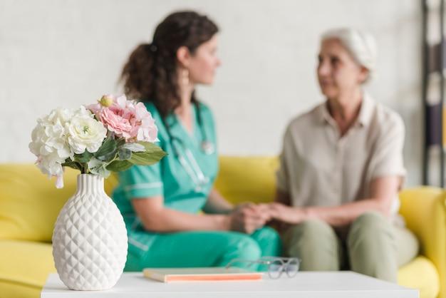 Florero delante de la enfermera y paciente femenino mayor que se sienta en el sofá Foto Premium
