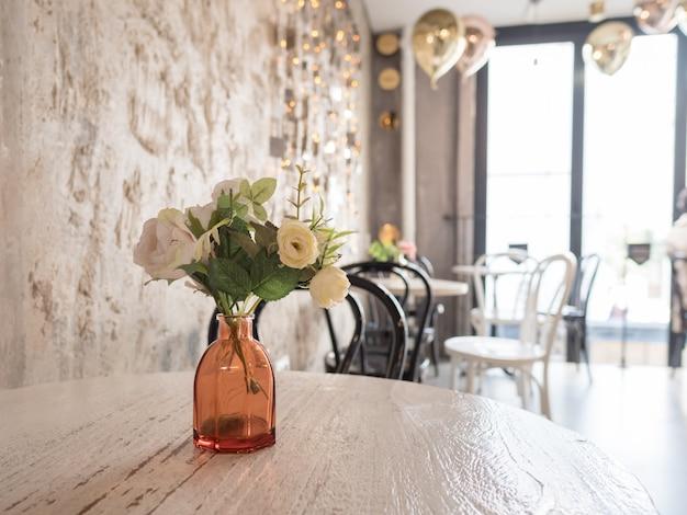 Florero con flores decorativas en mesa de madera. luz interior de la habitación Foto Premium