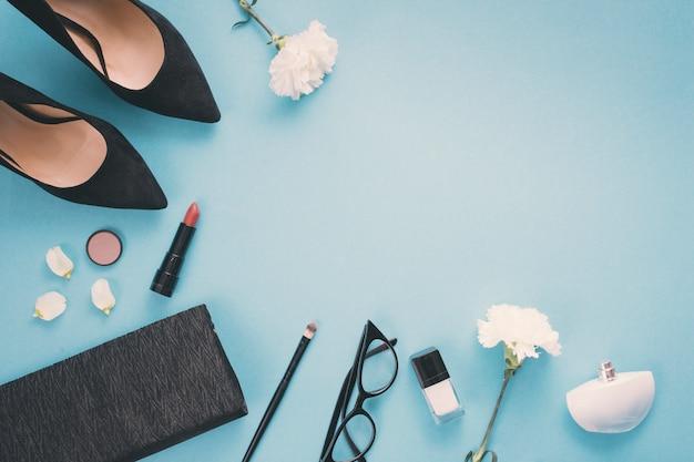 Flores blancas con cosméticos y zapatos de mujer en mesa. Foto gratis