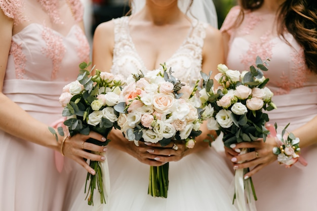Flores de boda, novias y damas de honor que sostienen sus ramos en el día de la boda. Foto gratis
