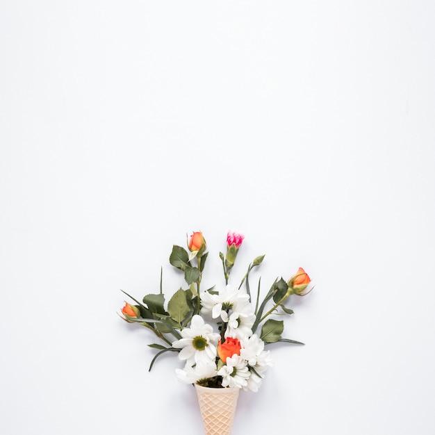Flores brillantes en cono de waffle en mesa Foto gratis