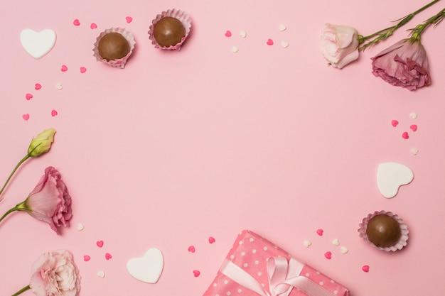 Flores cerca de caja actual y dulces de chocolate. Foto gratis