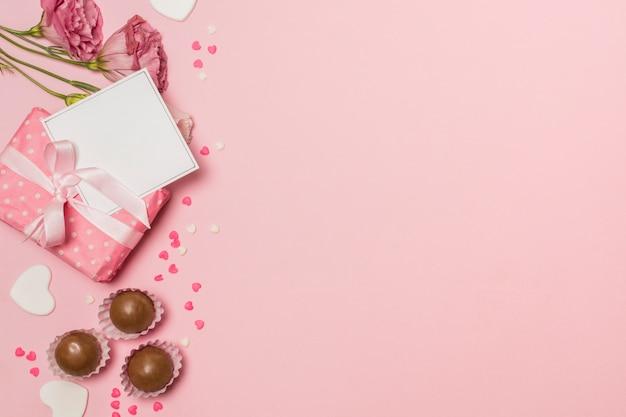 Flores cerca de tarjeta postal en caja actual y caramelos de chocolate. Foto gratis