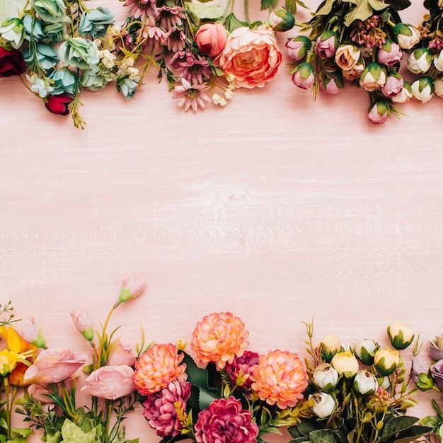 Flores de colores sobre fondo de madera rosa Foto gratis