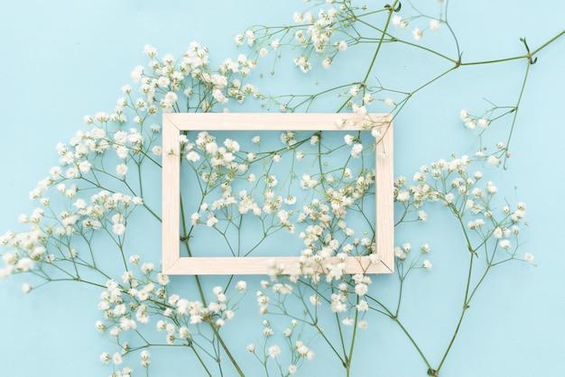Flores de composición romántica. flores blancas del gypsophila, marco de la foto en fondo azul en colores pastel. Foto Premium