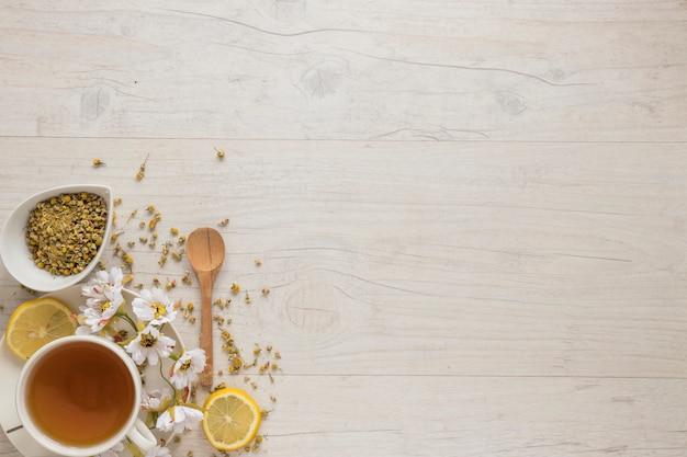 Flores de crisantemo chino secas y rodajas de limón con té de limón en mesa de madera con textura Foto gratis