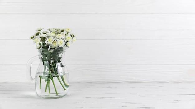 Flores de crisantemo dentro de la jarra de vidrio sobre fondo de madera blanco Foto gratis