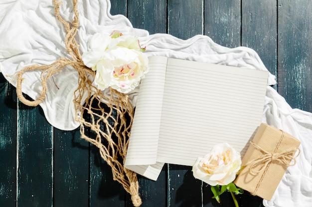 Flores con cuaderno vintage vacío y regalo Foto Premium