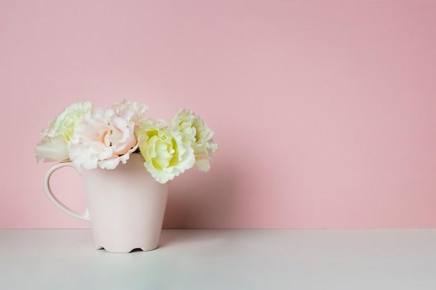 Flores elegantes en taza de té Foto gratis