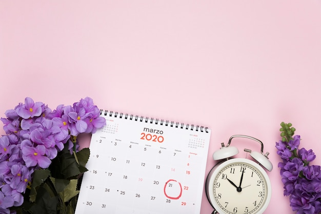 Flores de flor con calendario y reloj al lado Foto gratis