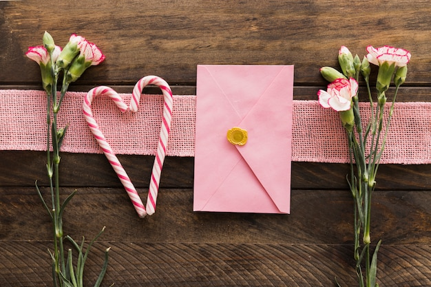 Flores frescas cerca de la cinta, sobre y bastones de caramelo. Foto gratis