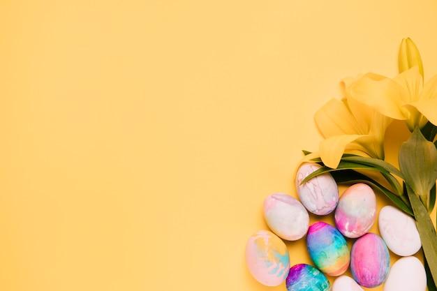Flores frescas del lirio con los huevos de pascua coloridos en la esquina del fondo amarillo Foto gratis
