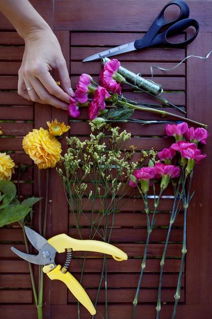 Flores y herramientas sobre la mesa, trabajo de floristería, vista superior de naturaleza muerta Foto Premium