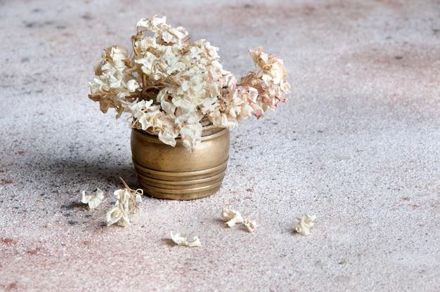 Flores de hortensias secas en un jarrón de latón Foto Premium