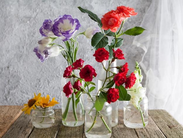 Flores en jarrones sobre una mesa de madera Foto Premium