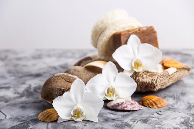 Flores de orquídeas blancas junto a piedras de mar y conchas sobre un fondo gris Foto Premium