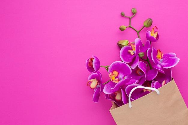 Flores de orquídeas en una bolsa de papel Foto gratis