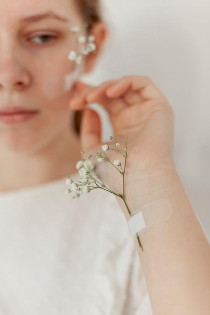 Flores pegadas en la mano de la modelo Foto gratis