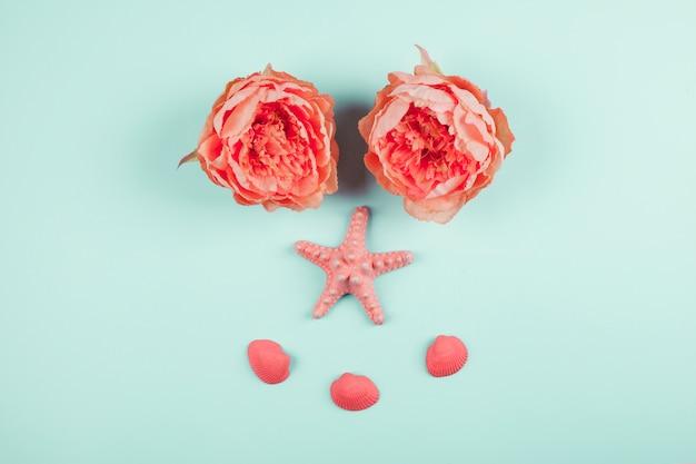Flores de peonias de coral pintadas; estrellas de mar y almejas sobre fondo de menta Foto gratis