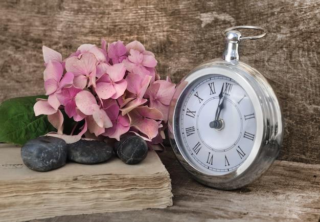 Flores, piedras y un reloj de bolsillo. Foto Premium