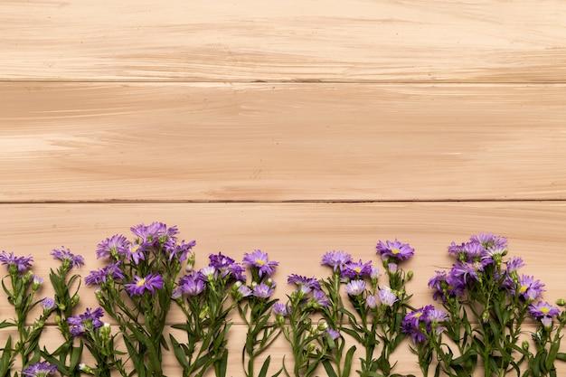 Flores púrpuras naturales sobre fondo de madera Foto gratis