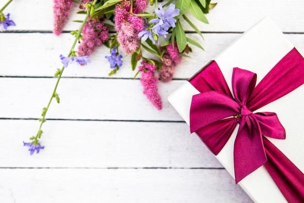 Flores y regalo sobre fondo de madera. Foto gratis