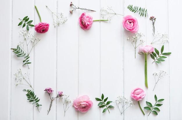 Flores rosas decorativas sobre superficie de madera Foto Gratis