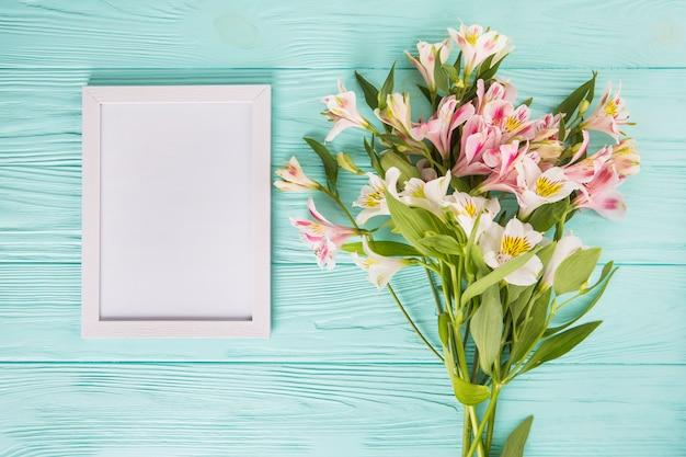Flores rosas con marco en blanco en mesa de madera Foto gratis