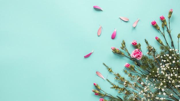 Flores rosas con ramas de plantas en mesa. Foto gratis