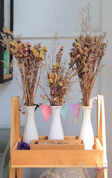 Flores secas en la decoración del florero en el estante de madera en el café. Foto Premium