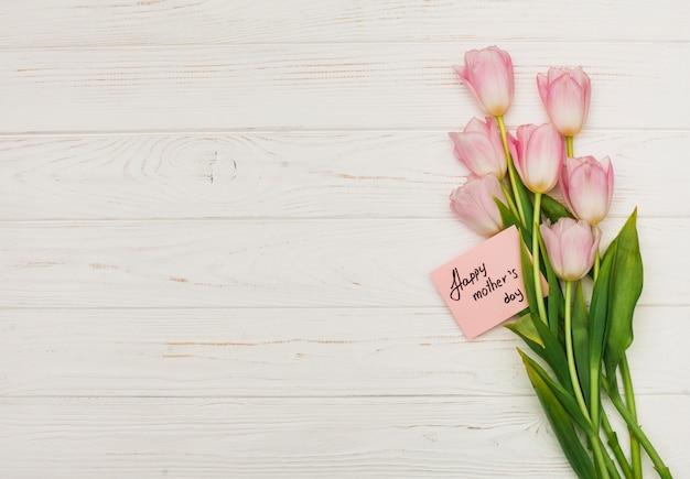 Flores con tarjeta feliz dia de las madres en mesa Foto gratis