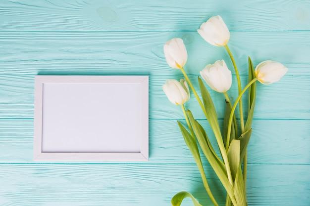 Flores de tulipán blanco con marco en blanco en la mesa Foto gratis