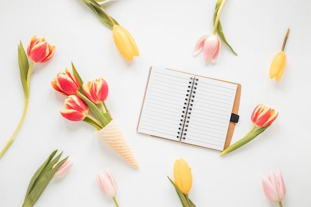 Flores de tulipán en cono de waffle con cuaderno en blanco Foto gratis