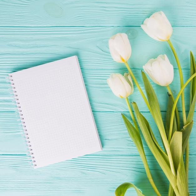 Flores de tulipán con cuaderno en blanco en mesa de madera Foto gratis