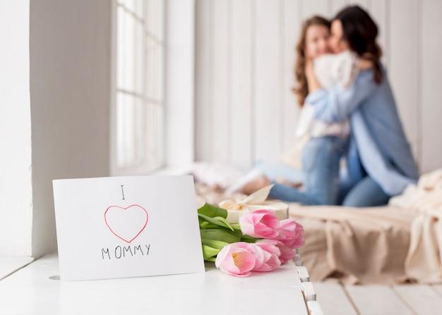Flores de tulipán y tarjeta de felicitación en mesa Foto gratis